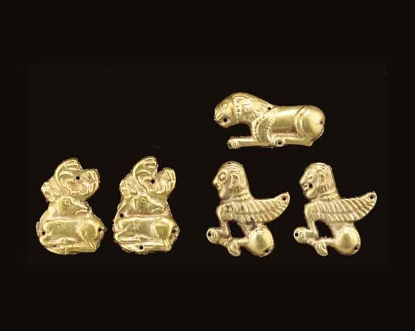 FIVE SCYTHIAN GOLD APPLIQUÉS   Circa Mid 5th Century B.C.   All die-formed, including one in the form of a reclining lion in profile to the left, double zig-zag on its mane; two in the form of a winged sphinx in profile to the left; and two in the form of a stag in profile to the left, its head turned back, each with perforations for attachment