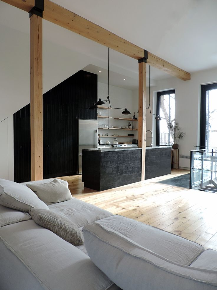 Montreal home renovation by 3/4 Fort . Open concept kitchen with black island
