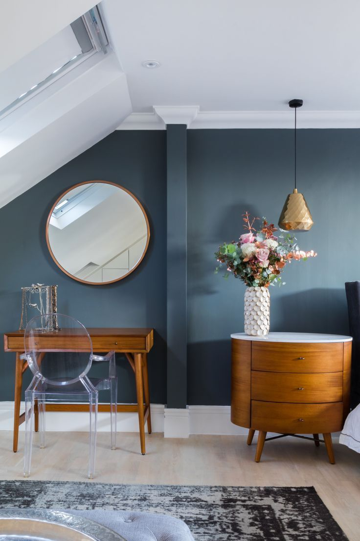 Mid century modern furniture blue paint on walls and round mirror