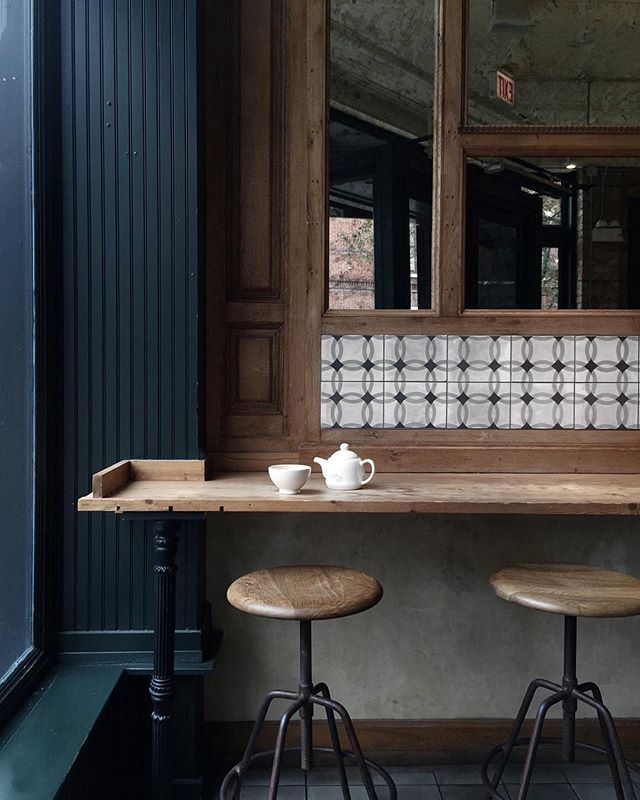 Beautiful colours and textures you could transfer into a kitchen setting-the inky blue, worn oak and black and white tiling as a trim or splashback | Wooden coffee shop bar seating with touches of tile