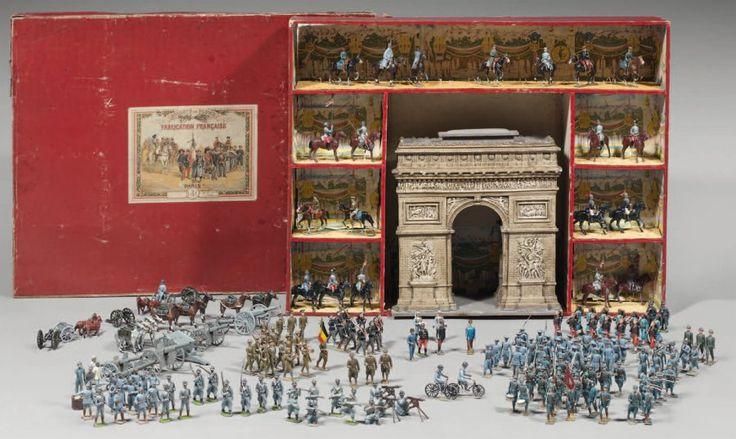 """""""Défilé de la victoire"""" : boîte de soldats de plomb de la marque : """"L C"""" avec abeille de la maison Lucotte, Paris, puis Margat de 1913 à 1928. Elle contient, au centre, l'Arc de Triomphe de l'Étoile, en bois et en plâtre peint, hauteur 34 cm ; autour, sept compartiments, dont le fond est peint avec des vues des Champs Élysées, qui contiennent vingt cavaliers. Dimension de la boîte 67 x 54 cm. Vendu aux #encheres le 14/10/10 par Thierry de Maigret"""