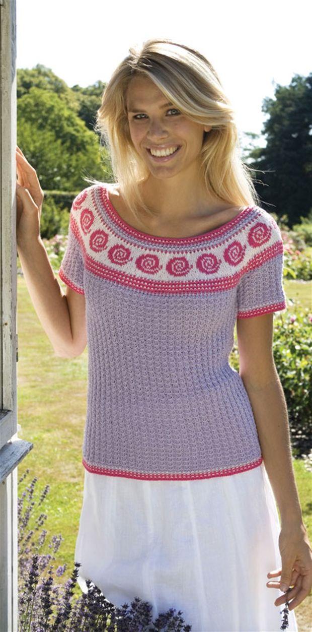 Den lyslilla bluse med abstrakt rosenmotiv er strikket i et let ribmønster forneden, mens bærestykket er strikket på rundpind.