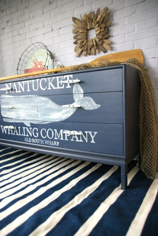 Chalk painted chest of drawers with a hand painted ship silhouette for a nautical themed bedroom.