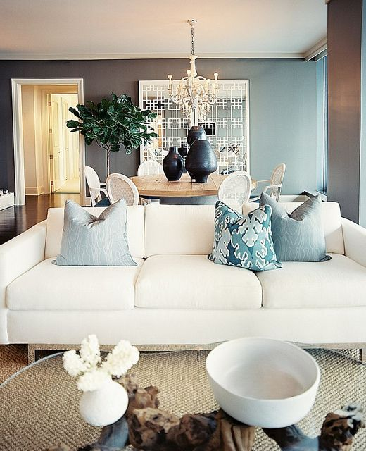 Grey-blue walls with sisal rug, driftwood coffee table and blue accents. Perfect for a glamorous yet comfortable seaside home.