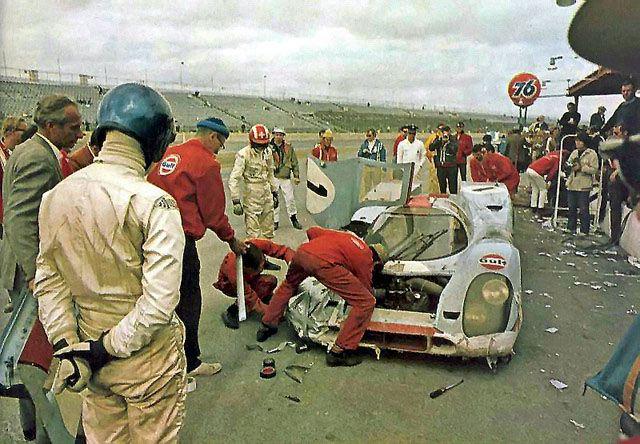 Brian Redman (blue helmet) and Jo Siffert (red & white helmet) study their #1 J.W./Gulf Porsche 917 at Daytona in 1970.