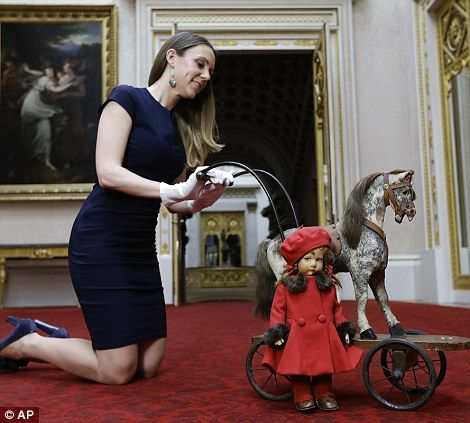 Exhibition curator Anna Reynolds displays a toy horse on wheels that Princesses Elizabeth and Margaret played with circa 1930s, and 'Pamela' a doll in a red beret