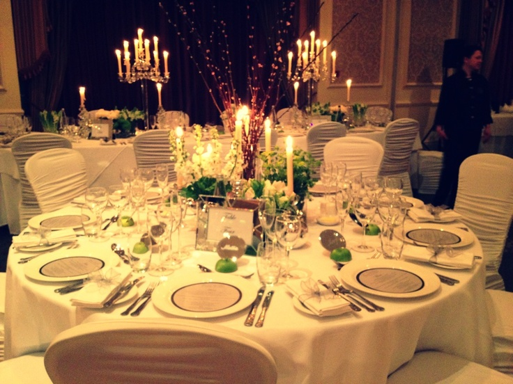 Classic look of crisp Irish linen with vases of single coloured flowers and Galway crystal candlesticks