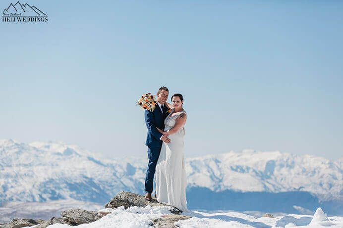 blue skies and snow. Bride and groom stand on The Ledge. Destination Heli weddings Queenstown.