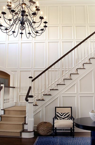Elsa Soyars: Formal entryway with white recessed panel wainscotting and seagrass stair runner.