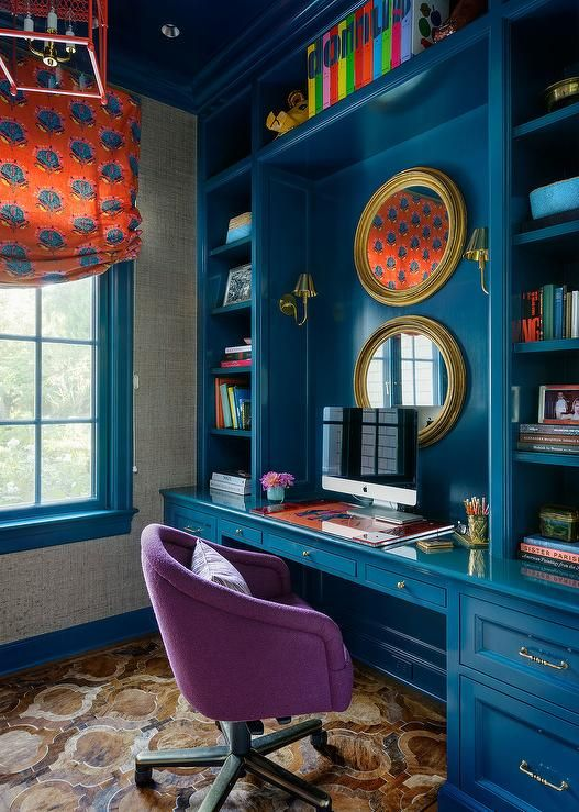 Contemporary home office features a glossy blue built in desk adorned with polished brass hardware paired with a purple rolling chair placed under blue built in shelves.