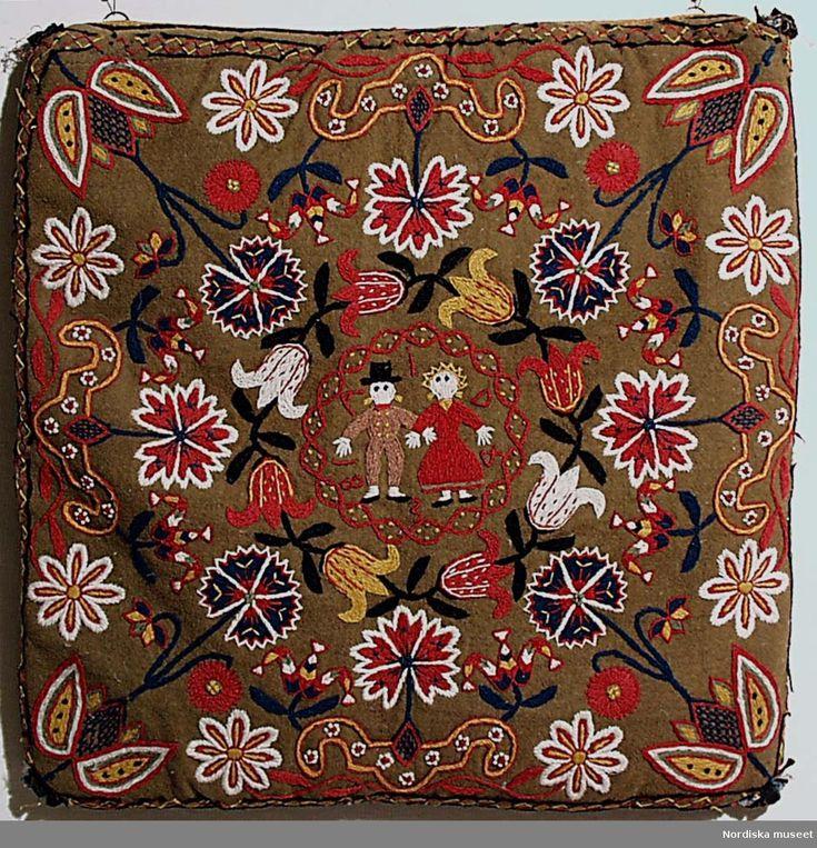 Dyna sannolikt bruddyna med fritt broderi på gulbrunt valkat ylletyg. I mitten ett brudpar inom en krans med bruden i röd klädnad och mannen i hög svart hatt samt broderad märkning A I D 1834 med rött ullgarn, utanför denna ytterligare en krans med svarta blad och tulpaner i rött, gult och vitt. I kanten större blommor på stjälk och ett ornament i var sida. Broderiet mycket skickligt komponerat och utfört, med ullgarn i ensidig plattsöm, schattérsöm, stjälksöm och flotterande bottensöm samt…