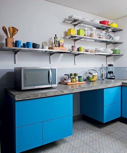 Para conseguir leveza na cozinha pequena, o arquiteto Vitor Penha apostou em poucos armários e muitas prateleiras. A marcenaria não ocupa toda a área abaixo da bancada e nem vai até o chão