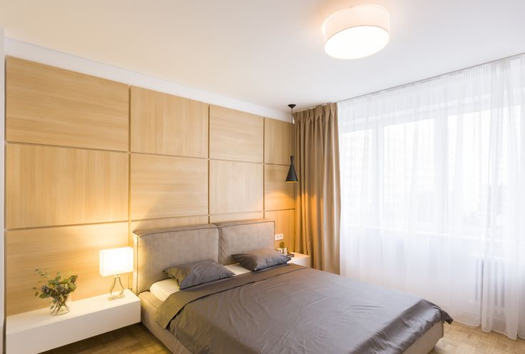 Cool bedroom with grey bed and wood wall, white nightstand and modern lighting.