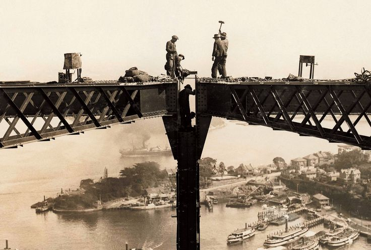 Image of a partly constructed bridge with workers standing on steel girders high above the harbour. Bridging Sydney - museum of Sydney exhibition