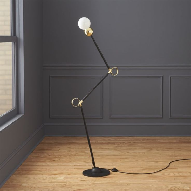 light angles. Two-tone lamp shines sculptural in exaggerated angles and gleaming brass accents. Iron frame contrasts modern matte black and shiny brass that zigzags and intersects graphic. Topped with an exposed bulb—lamp is the definition of art at work.