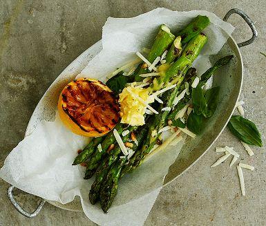 Fixa förrätten på grillen! Grön sparris är en sann vårprimör och oerhört mumsig att grilla. Den som vill bryner först smöret, låter det kallna och blandar sedan med citron, salt och peppar. Pikant parmesanost och knapriga pinjenötter fulländar smakerna.