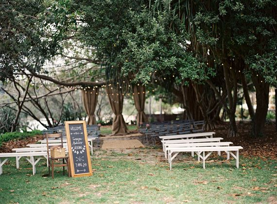 Australian wedding | photo by Byron Loves Fawn Photography |   Ceremony under the trees with bench seats  hessian/ burlap backdrop