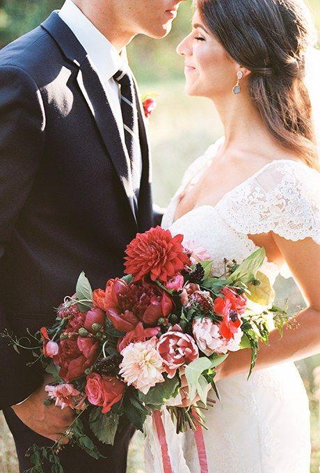 Bruidsboeket met dahlia's in donkerrode kleuren die perfect passen bij een bruiloft in de herfst of winter.
