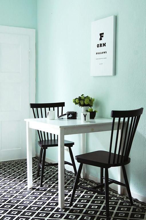Wo kein Platz für ein separates Esszimmer ist, reicht auch eine kleine Ecke für ein Candlelight Dinner aus. Die mintgrüne Wand und der schwarzweiße Teppich bringen eine Spur Retro-Feeling in die Küche.