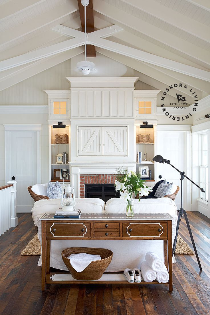 The television is hidden behind paneled doors and flanked by brightly lit, built-in bookshelves in this charming family room from muskokalivinginteriors.com