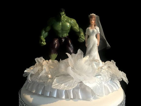 This Incredible Hulk wedding cake topper has the Incredible Hulk and a bride.   The Incredible Hulk is green wearing dark purple pants and the bride is wearing a white dress and a white veil. The couple are standing on a white oval base which has white flowers at their feet and trim with white ribbon.   The base and figurines are made of plastic. This Incredible Hulk wedding cake topper is 6 inches tall and is 4 x 6 inches in diameter.  This is a perfect wedding cake topper for the…