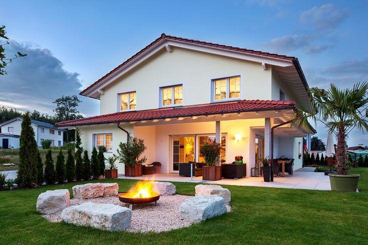 Ein massives Einfamilienhaus im mediterranen Stil mit moderner Inneneinrichtung und einem großen Garten mit einer kieselbelagerten Feuerstelle präsentiert Haus Lehmann   – Tinchen Ko