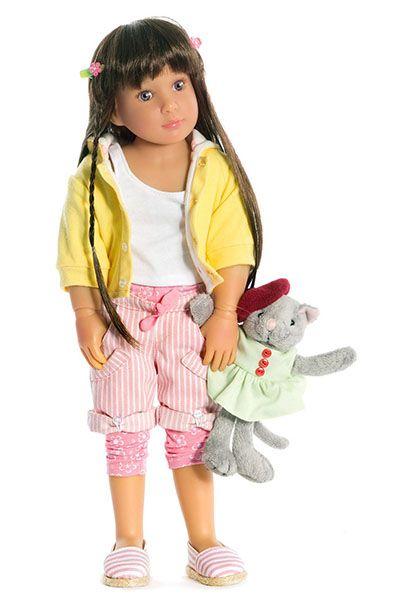Jolina es una muñeca alemana que tiene una bonita cara con unos ojos azules que te enamorarán. Sus labios están pintados para darla un aspecto más real. Tiene el pelo largo y moreno, realizado en fibra sintética de alta calidad y peinado con dos pequeñas trenzas. Viste una  chaqueta de color amarillo claro de verano, una camiseta blanca, leggins con estampados florales y pantalones cortos de rayas a juego con alpargatas también de rayas. #Dolls #Doll #Bonecas #Poupées #Bambole #KidznCats