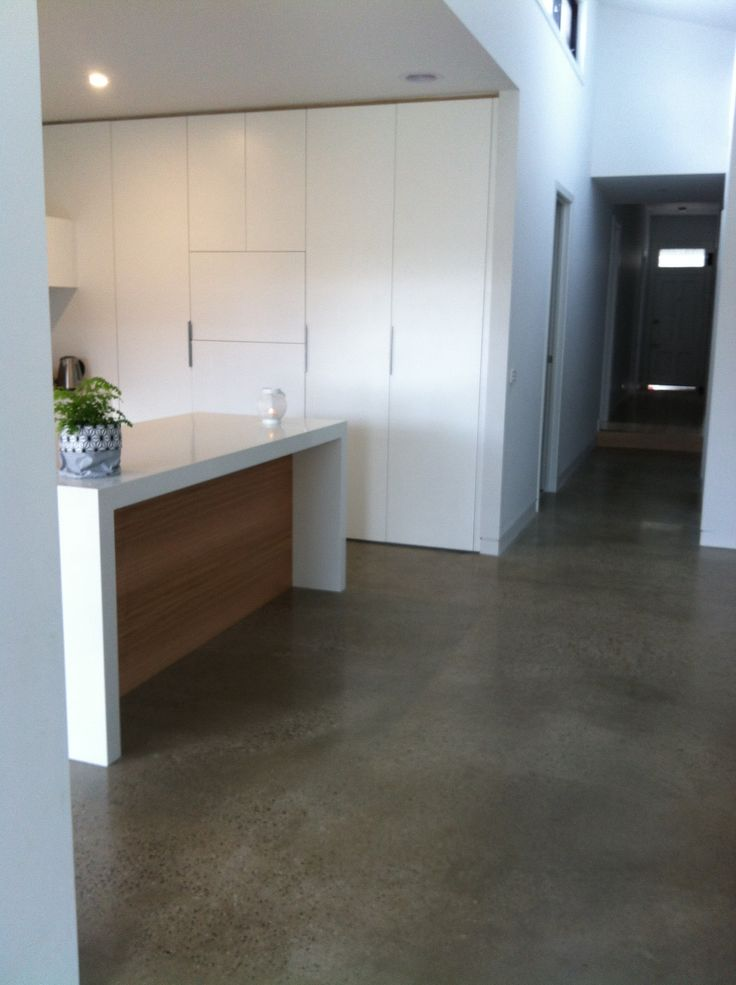 Kitchen with polished concrete floor, white stone benchtop and Tasmanian oak