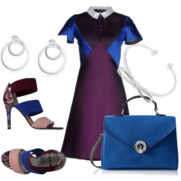 Outfit originale negli accostamenti cromatici. Abito di linea dritta, maniche corte e collettino bianco, nei colori del viola, bluette e nero. Sandali alti tacco a stiletto con fasce colorate, borsa bluette con un manico e tracolla nera. Accessori in acciaio.