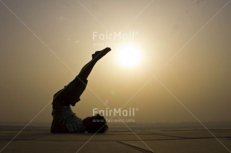 | @FairMail - Fair Trade Cards - IKSD-0857 | Activity, Asia, Backlit, Doing yoga, Evening, Garden, Horizontal, India, Light, Low angle view, One boy, Outdoor, People, Shooting style, Silhouette, Sky, Sun