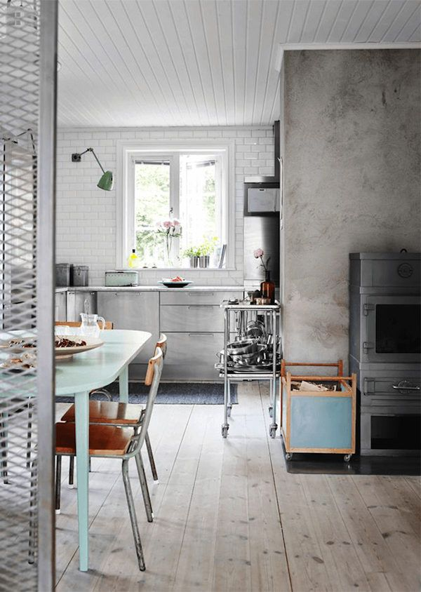 Subway tiles and vintage school chairs in the dining area of an industrial inspired Swedish home . Jonas Gustavsson / Charlotte Frey Sviden.