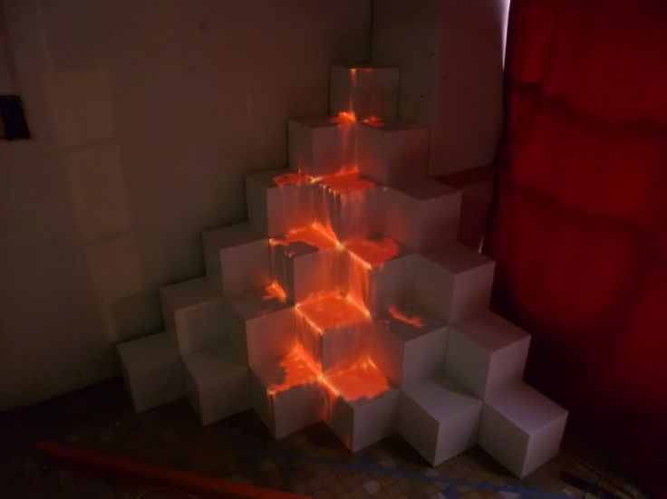 Video mapping installation : Lava flowing effect on a pile of cubes.