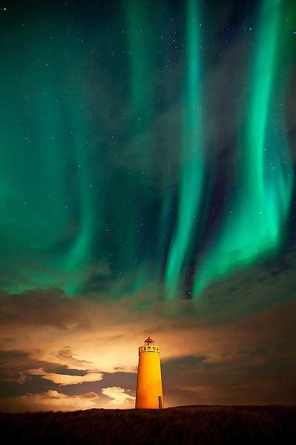 A light house in Iceland dancing with the northern lights.