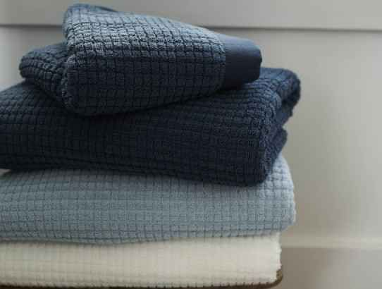 Buy towels in darker colors, like navy or charcoal.