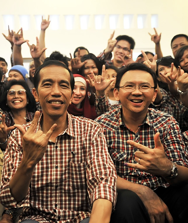 Jakarta governor candidate Joko 'Jokowi' Widodo, second front left, and Basuki T. 'Ahok' Purnama, front second right, cheer with supporters on Jl. Borobudur in Jakarta, on July 11, 2012. According to preliminary results released by the Indonesian Survey Institute (LSI) Jokowi was in the lead with 42.3 percent of the votes. (Antara Photo/Prasetyo Utomo).