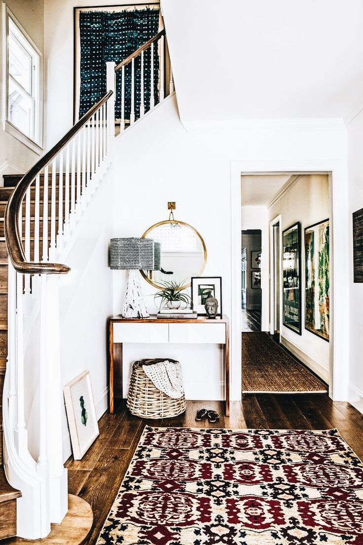 A grand yet bohemian staircase, love he fresh white paired with natural wood. Can we talk about how much character this rug brings this entryway?! #bohemian #staircase #rug