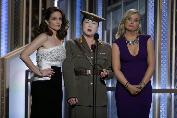 ゴールデングローブ賞授賞式で司会のティナ・フェイ(左)とエイミー・ポーラー(右)に挟まれ、北朝鮮人にふんして登壇したマーガレット・チョー=11日、米ロサンゼルス(ロイター)