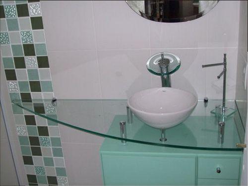 A bancada de vidro dá mais leveza na decoração para banheiros muito pequenos. Um truque usado para aproveitar espaço foi fazer essa bancada de canto.