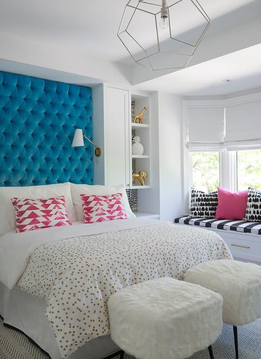 A room any teen would adore, this contemporary girl's bedroom features a tall sapphire blue velvet tufted headboard recessed behind a bed dressed in a gold polka dot duvet color accented with pink triangle print pillows lit by brass headboard sconces.