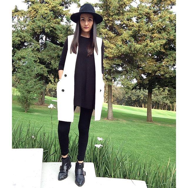 leggings negros, blusón  negro, botas y chaleco blanco