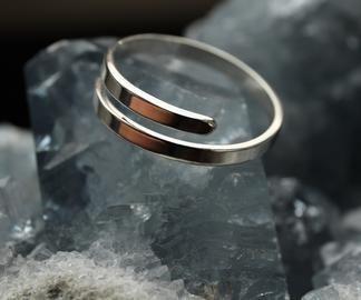 Dit is een zilveren replica van een gouden ring uit de bronstijd (1500-800 jaar voor het begin van onze jaartelling).