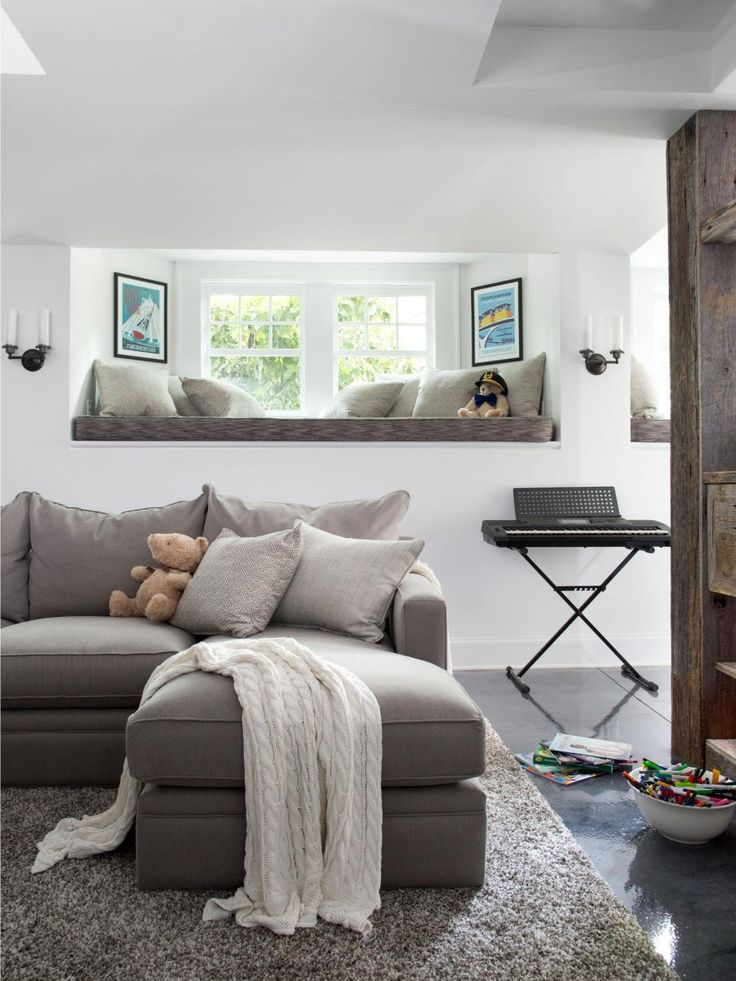 After the hefty expense of the remodel, the Winters decided to stick with a timeless color palette they could mix up without any major expense. Overall, the basement is made up of warm grays and a cool shade of white. To keep the space from feeling matchy-matchy, a variety of gray tones including greige, charcoal and brown gray were used on the concrete stain, sofa upholstery, pillows and window seat upholstery.