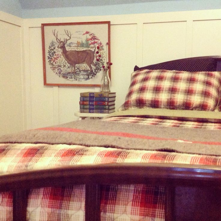 Log cottage iron bed with plaid quilt, needlepoint deer, and a stack of Collier's Junior Classics.