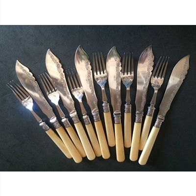 Antique silver-plated fish/dessert cutlery.  This 12-piece Victorian set of bone-handled cutlery (6 knives, 6 forks) was manufactured by Thomas Turner and Company in Sheffield, England, in the late 19th century.  It is hallmarked on the back of each knife.  The length of the knife blade is engraved with a delicate line of floral tracery and a scrolled element of the design is echoed on the fork.  Both knives and forks have an embossed band of vines and berries, which join the bone handles to…