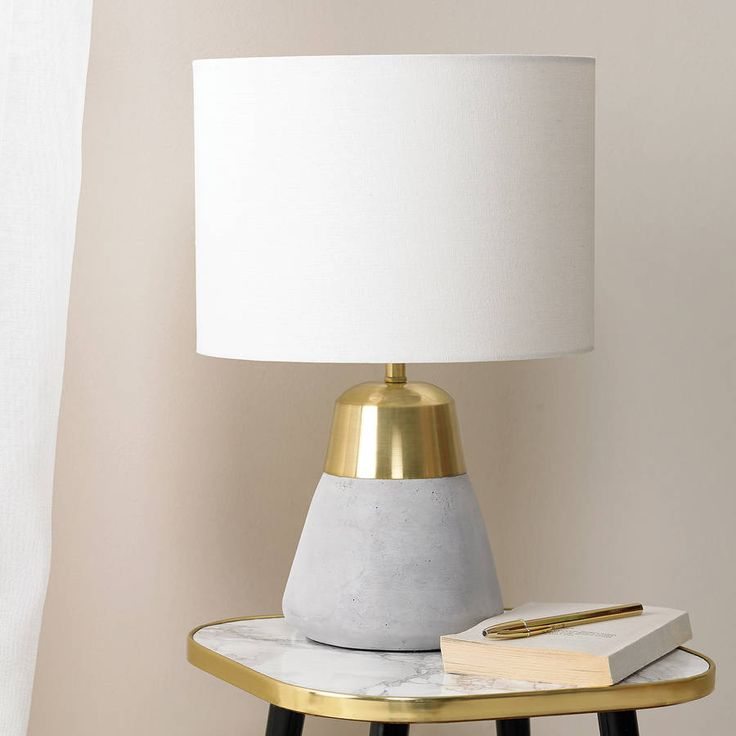 An extremely unique and striking concrete table lamp which is bound to make an eye catching impact on your interior this Autumn.Cast in a stunning polished concrete base and finished with a beautifully co-ordinating gold collar detail and topped with a complimentary ivory linen drum shade, this quality table lamp is guaranteed to make a bold statement to any contemporary, modern decor. Perfect as a bedside lamp or placed on an occasional table or console. Takes 28W eco halogen bulb, 8W…
