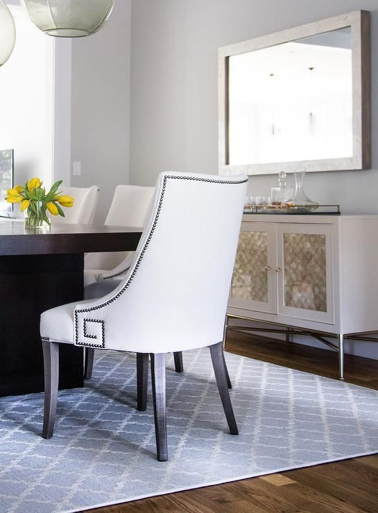 Centered On A Blue Trellis Rug An Espresso Stained Dining Table Is Surrounded By White