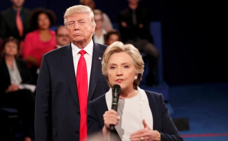 Pictures of the year 2016 | Reuters.com  Photographer Rick Wilking Location ST. LOUIS, United States Reuters / Monday, October 10, 2016 Donald Trump listens as Hillary Clinton answers a question from the audience during their presidential town hall debate at Washington University in St. Louis, Missouri, October 9, 2016. REUTERS/Rick Wilking