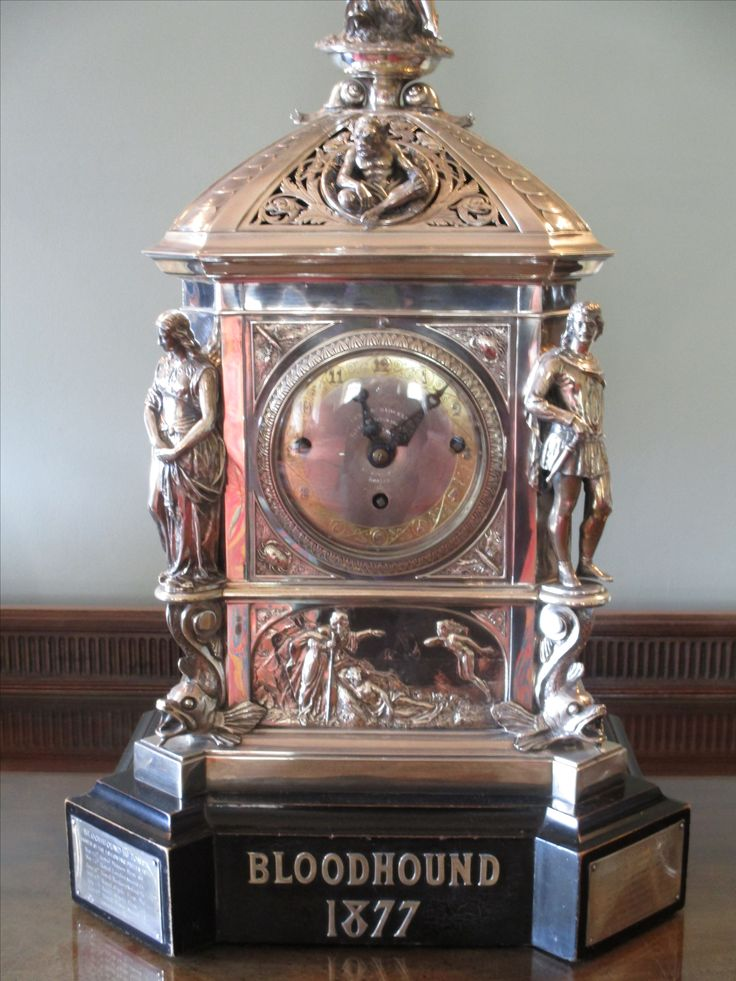 Silver mantle clock by Lund & Brockley, London.  Case is cast and chased with dolphins and figures of Venus.  Designed by A. Crichton.  Design achieved £50 prize.  Commissioned by the 3rd Marquis of Ailsa, using prize money from his racing yacht 'Bloodhound' in 1877.  Yacht designed by Fife of Fairlie.