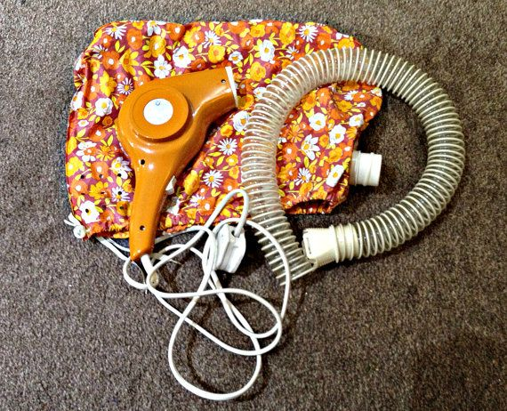 Wow a blast from the past when styling your hair! Presented here is a 1960s 350 watt hair dryer in perfect working order in a bright orange colour. It was made for the Boots Company in England  The hand held hair dryer connects via a hose to a soft plastic cap covered in a funky flower pattern, also in shades of orange and yellow. The hood covers the hair completely for that vintage hair styling experience. It has 2 settings hot and cool; hot to dry the hair and cool to set the style. The…