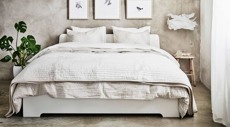 Lit blanc et linge de lit en beige et blanc.